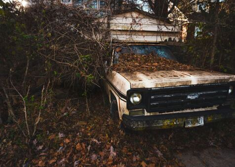 Old junk Chevy truck with modified roof in woods to be taken by junk removal service